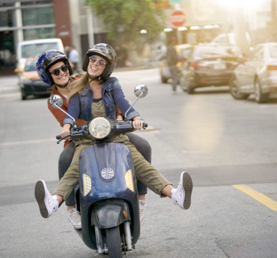 Happy young women riding scooter together in city